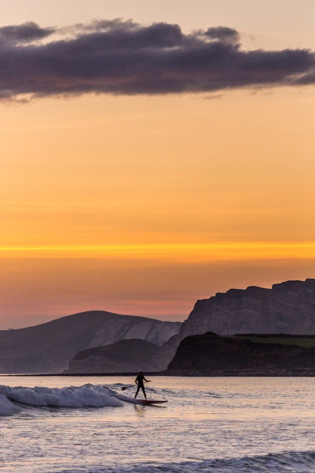 Paddle boarder in Kimmeridge Bay with a orange sunset behind